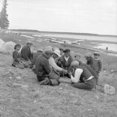 The residents of Great Whale River (Quebec) enjoy a game of chance as a pastime / Les habitants de Great Whale River (Qubec) s'amusent  un jeu de hasard pour passer le temps (BiblioArchives / LibraryArchives) Tags: canada toys quebec lac games du qubec northern et nord bac residents jouets jeux libraryandarchivescanada habitants gameofchance indiennes bibliothqueetarchivescanada greatwhaleriver jeudehasard 1949indian sjbailey affairsaffaires
