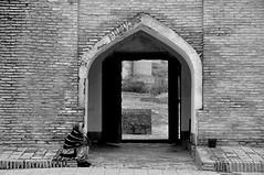 At the Gate of the Old Madressa (Le*Gluon) Tags: street bw woman wall bricks tajikistan exit d90 madressa tadjikistan gissar tamron18270