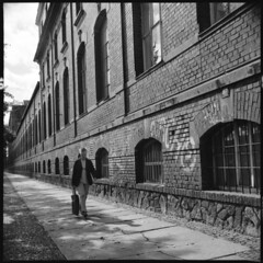 . (Martin Ritter) Tags: street city windows light urban blackandwhite woman building stone wall analog mediumformat walking 50mm lomo iso400 bricks citylife streetphotography geometrical left urbanlife perspectiv lefttoright lomolubitel166b intoview rolleirpx400 rolleirpx