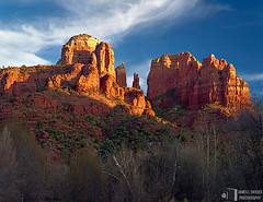 Cathedral Rock, Last Sunlight (James L. Snyder) Tags: park autumn trees sunset red arizona orange usa sunlight southwest green fall rock horizontal wall clouds last sandstone december butte afternoon shadows natural spires bare country rocky sedona sunny grand bluesky canyon brush cliffs formation nationalforest craggy valley strong late rough deciduous majestic crags bushes shrubs scrub 2009 magnificent rugged cathedralrock damp gleaming pinnacles towering crumbling cirrus oakcreekcanyon riparian dormant lofty monumental sidelighting moist shaded eroded chaparral grandeur verdevalley coarse coconinonationalforest magiclight redrockcrossing yavapaicounty artistslight