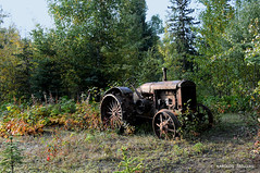 OLD TRACTOR IN MCBRIDE . . .  (CANADA, BRITISH COLUMBIA, MCBRIDE) (KAROLOS TRIVIZAS) Tags: canada britishcolumbia mcbride tractor wheels wood old vintage field cultivation forest abandonment technology
