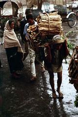 11-640 (ndpa / s. lundeen, archivist) Tags: street wood city nepal people woman man color men film 35mm asian asia southeastasia candid nick citylife streetphotography streetlife 11 backpack barefoot kathmandu nepalese shawl rickshaws 1970s bundle load 1972 katmandu firewood himalayas carry burden sliceoflife carrying nepali southasia dewolf nickdewolf photographbynickdewolf reel11