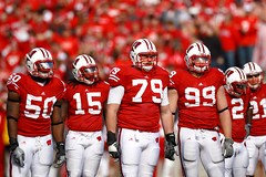 Front Line (Todd Klassy) Tags: red people white game men uw sports students horizontal wisconsin standing season outdoors football team athletics emotion cardinal action unity battle iowa gameday madison numbers badgers angry stockphotos editorial strength uniforms jerseys players fullframe adidas ncaa amateur universityofwisconsin groupofpeople wi defense huddle helmets teamwork collegefootball stockphotography offense buckybadger big10 royaltyfree colorimage shouldertoshoulder camprandallstadium bigtenconference division1a wisconsinphotography faceguards wisconsinphotographers toddklassy universityofwisconsinmadison athleticprogram