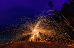 Burning steel wool on stone near the beach. (Nuttawut Uttamaharad) Tags: abstract art beach beautiful boy bright burn circle color danger dangerous energy fire fireworks flame glowing heat hot image light long man motion nature night orange outdoors pattern play red rock round steel stone swirl texture trail vibrant wool yellow