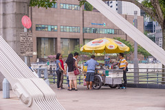 Ice Cream Stall at End of Cavenagh Bridge (danliecheng) Tags: cavenagh rafflesplace singapore attractions bread bridge buildings buying delicious desert eating food icecream people popular sandwich selling stall street tourists travel tricycle umbrella visit
