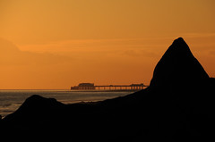Piered layers (crusader752) Tags: sunset sun beach silhouette pier worthing rocks boulders beaches lowtide setting