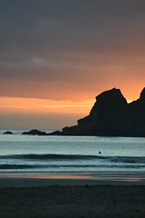 Surfing at Sunrise (djchphotography) Tags: sunset ocean beautiful colorful orange pink blue silhouette waves water west coast purple sandy shortys shorties sharkies rock cliffs color layers sky atmosphere beauty