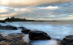 Dunstanburgh Castle (EmmaBoiston) Tags: blue sky sun white black reflection green castle water clouds speed nikon rocks waves slow northumberland shutter british effect milky isles britian dunstanburgh d5100