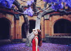 A Lilac Dream in Spring (Amanda Mabel) Tags: flowers red portrait brown motion tree castle nature hair petals spring movement focus seasons dress purple dream falling lilac naomi magical quadrangle jacarandatree amandamabel amandamabelphotography alilacdream