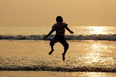 jumping jack! ([s e l v i n]) Tags: boy india beach water silhouette fun jump jumping bombay mumbai simeon enjoyment simu versova versovabeach boyjumping ©selvin