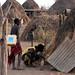 NIDs volunteer Haile Dooch stoops before a Karo hut inquiring children under five-Hamer District