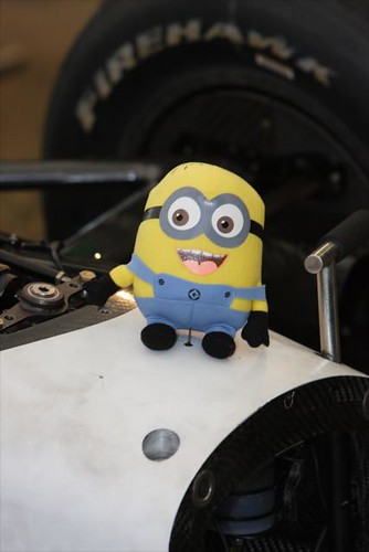 "A minion character from the movie ""Despicable Me"" sits on a car"