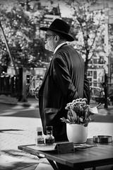 esperando (Mauro Esains) Tags: seor persona adulto espera bar flores mesa sombrero saco aire libre blanco y negro holands monocromtico nikon bokets bokeh