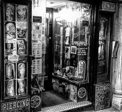 """Piercing&Tattoo Shop"" (giannipaoloziliani) Tags: ricky skulls city downtown flickr vicolidigenova genova vicoli view italy narrowstreet vetrina pictures noire projects window piercing blackandwhite black monochrome oldshop shop tattoos piercings"