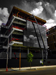 People in glass houses (Steve Taylor (Photography)) Tags: construction scaffold scaffolding window crane black green yellow red mauve purple selectivecolour glass newzealand nz southisland canterbury christchurch cbd city tree cloud sky trafficlight