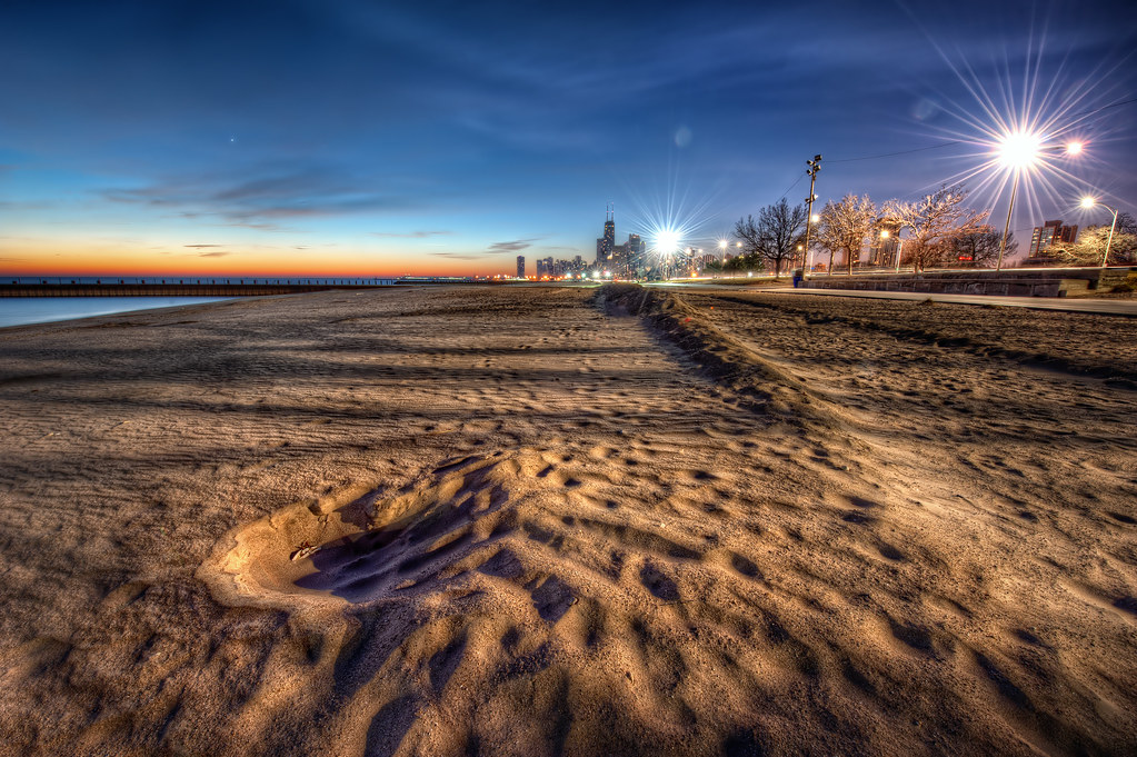 A wave of sand along the lake shore path during a clear Chicago sunrise.