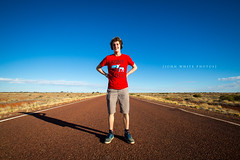 Highway (john white photos) Tags: road red male standing highway desert flat australia teenager outback remote middle southaustralia bitumen centralaustralia