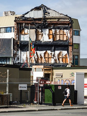 Bared Walls and Bared Legs (Steve Taylor (Photography)) Tags: architecture graffiti tag streetart art building office fence chainlink window wall roof earthquake 22february2011 broken damage quake smashed weird strange odd brick woman lady newzealand nz southisland canterbury christchurch cbd city fletcher ripped tattered tatters bare legs backpack headphones wow