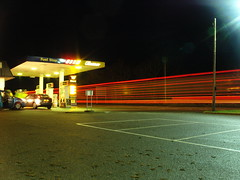 Wall of Red Lights at Evelix Services (Red Storm Rising) Tags: road park trees winter red blur tree car night effects lights scotland highlands long exposure garage parking pump lorry pines remote trucks tall petrol streaks services dornoch lorries gleaner lighttrail hgv