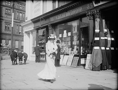 Striding along Sackville Street (National Library of Ireland on The Commons) Tags: flowers ireland dublin hat children bolts cigars material cloth chronicle oconnellstreet irishpeople irishtimes leinster tobacconist sackvillestreet newsagents averill furstole nationallibraryofireland coffeerooms jjclarke charlesbyrne newsposters dublinunitedtramwayscompany sportingchronicle royalbanklimited cathaluabroin johnjosephclarke drjjclarke clarkecollection dublintramways