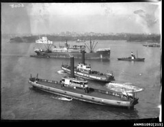 Ferries KALANG, KOONDOOLOO underway with a warship (possibly HMAS CANBERRA) and HMAS ANZAC at anchor, Sydney Harbour