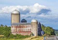 Rural New York Barn (Kenneth Keifer) Tags: clouds landscape newyork red road unitedstates agricultural agriculture barn concretesilo country countryside faded farm farming highway leaning metalroof nature old rugged rustic scenic shelter silos tinroof vintage weathered wood wooden worn