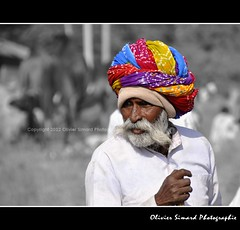 Pushkar Camel Fair (Olivier Simard Photographie) Tags: portrait people india color evening soleil colorful market shepherd couleurs picture fair tomates moustache camel turban sikh mam pushkar march foire rajasthan barbe homme visage brahma inde streetshot candidshot berger indu dromadaire chameau sadri tissus camelfair pushkarcamelfair troupeau aravalli scnederue toffes indou pushkarkamela blinkagain puskarmela  kartikpurnimafullmoon oliviersimardphotographie