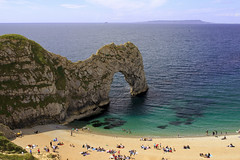 Durdle Door (Martins Skujans) Tags: ocean travel blue light sea sky people cliff cloud sun colour green beach nature water sunglasses rock composition swim canon coast sand raw day afternoon view bright turquoise tide hill tourist cliffs hills pro lonely colourful jpeg isle durdledoor canoneos600d martinsskujans