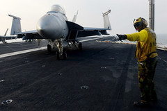 A Sailor directs an F/A-18F at sea. (Official U.S. Navy Imagery) Tags: heritage america liberty freedom commerce unitedstates military navy sailors fast worldwide tradition usnavy protect deployed flexible onwatch beready defendfreedom warfighters nmcs chinfo us5thfleetareaofresponsibility sealanes warfighting preservepeace deteraggression operateforward warfightingfirst navymediacontentservice