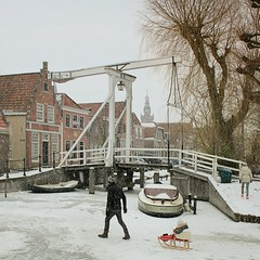Enjoying the snow in picturesque Monnickendam (Bn) Tags: bridge winter sun snow haven holland tower classic dutch kid iceskating father sneeuw skating under thenetherlands colores wintertime sled marken nostalgie volendam speedskaters sledge waterland slee ijs schaatsen iceboats mo