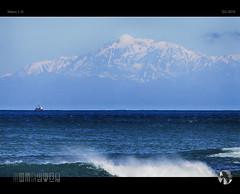 Between Mountains and the Deep Blue Sea (tomraven) Tags: mountain snow snowcapped fishingboat boat tomraven aravenimage sea sky telephoto wave surf blue q32016 nikon1 j5
