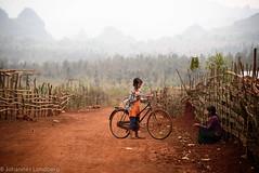 Girl with bike (JohannesLundberg) Tags: burma girl countryside ngwedaung red myanmar bike roadside expedition fence kayah myanmarburma mm