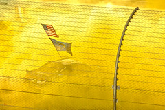 Noxious Yellow (dlholt) Tags: yellow racecar fence action flag smoke americanflag racing celebration nascar burnout facebook penske penskeracing homesteadmiamispeedway worldcars keselowski bradkeselowski