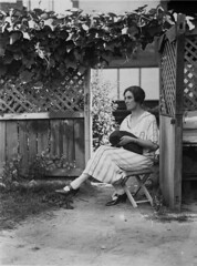 Unidentified women sitting on stool in garden with black cat, 1930s, Sam Hood (State Library of New South Wales collection) Tags: statelibraryofnewsouthwales