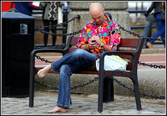 Flower Power (* RICHARD M) Tags: street feet fashion shirt liverpool bench concentration chains clothing candid character seat bald cellphone style clothes cobblestones barefoot mobilephone barefeet cobbles loud flowerpower albertdock oblivious merseyside technicolour barefooted