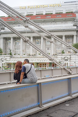 Young Intimate Couple Talking on Cavenagh Bridge (danliecheng) Tags: cavenaghbridge fullertonhotel rafflesplace singapore attractions bridge buildings couple evening intimate leaning lifestyle people sitting suspension talking tourists travel visit young