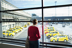 Wait a moment, they are not taxis!  Rob Watkins 2012 (Aland Rob) Tags: park street travel windows red woman cars window girl lines tarmac yellow standing out denmark photography long fuji top candid security terminal safety traveller vehicles hanging jumper fujifilm lonely parked carpark shoulder staring parallel handbag runway stands converge kastrup kbenhavns converging kpenhamn x100 lufthavne streettogs