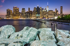 On the Rocks (Amar Raavi) Tags: brooklyn brooklynbridgepark buildings downtownmanhattan eastriver longexposure lowermanhattan manhattan nyc newyork newyorkcity oneworldtradecenter skyscrapers dusk water waterfront dumbo skyline unitedstates freedomtower financialdistrict cityscape architecture city downtown outdoor riverfront cloudy pier1 rocks