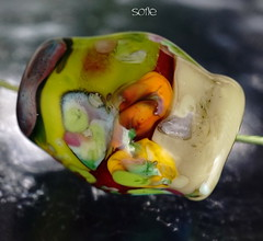 Sofie (Laura Blanck Openstudio) Tags: openstudio openstudiobeads glass hadmade lampwork beads single focal bead necklace pendant jewelry big holes choker murano whimsical funky odd abstract asymmetric colorful multicolor nugget rock pebble stone wearable faceted made usa fine artsartisan artist winner show published festival transparent frit lilac lavender violet grape purple plum copper green turquoise blue aqua orange coral red ocher maize beige almond sand burgundy bordeaux wine maroon chartreuse parrot kiwin lime yellow