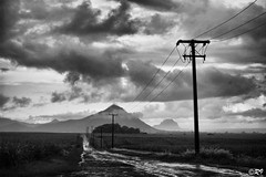 On the road to Flic en Flac beach - Mauritius Island (Ghoul-Seine) Tags: road sky bw white mountain black rain clouds zeiss 35mm landscape island dramatic epson mauritius f28 rd1s cbiogon cbiogont2835 ghoulseine ramjanally