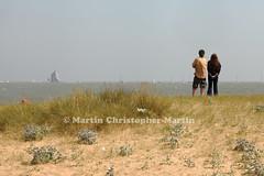 People watching the sea. (martin christopher-martin) Tags: boat ship sea horizon people man woman deckchair dune sand grass weeds seaweed sails clacton beach sky