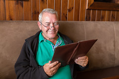 Smiling senior man reading a restaurant menu (Semmick Photo) Tags: green male man person smile adult brown brunch casual caucasian choice choosing customer decide decision dining dinner eatout elderly enjoy excitement glasses goout grey happy holding indoors jacket leisure looking lunch mature menu menucard menuoftheday old older one ordering pensioner read reading readingglasses restaurant search selection senior seniorcitizen sitting smiling