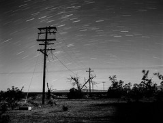 Stars (joshuammulligan) Tags: california longexposure blackandwhite film night analog stars landscape route66 fuji desert awesome wires highdesert mojave western neopan 100 analogue telephonepoles desolate mojavedesert acros startrail etrsi bronice