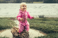 Simple Pleasures (A J Thackway) Tags: muddy puddles cosmeston lakes windy weather southwales valeofglamorgan cymru wales cardiff penarth canon 6d ef24105mm f4l simple pleasures splash splosh stomp water droplets spray happy laugh emotion baby youth toddler smile beam joy summer august rain waterproof jacket pink countryside uk united kingdom excitement excited girl