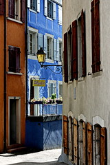 la maison bleue (overthemoon) Tags: switzerland suisse schweiz svizzera romandie vaud nyon buildings oldtown rive architecture blue faades windows shutters sunlight streetlamp gallery railing geraniums streetcorner