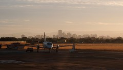 Adelaide skyline from Adelaide Airport with turboprop plane (Adriano_of_Adelaide) Tags: city morning shadow tarmac skyline plane sunrise airplane airport aeroplane apron adelaide cbd propeller southaustralia runway turboprop centralbusinessdistrict taxiing adelaideairport propellerplane distantskyline distantcity