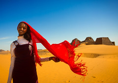 Young Sudanese Woman In Front Of The Pyramids And Tombs In Royal Cemetery, Meroe, Sudan (Eric Lafforgue) Tags: africa portrait sky woman cute history archaeology nature cemetery smiling horizontal architecture outdoors photography sand day veil desert pyramid wind northafrica soedan sudan bluesky custom multicolored ancientcivilization khartoum nubia royalty scenics soudan saharadesert northernafrica meroe realpeople colorimage blackskin onewomanonly lookingatcamera beautyinnature buildingexterior merowe 8263 aridclimate  1people onegirlonly szudn sudo  builtstructure northernsudan pyramidsofmeroe northsudan blackpharaohs      xuan eri8263
