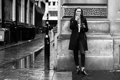 Smokers Corner (Cliff.j) Tags: woman girl smoking street candid glasgow corner rain reflection wet pavement phone eye contact city stare inhale contrast bw cigarette look stranger sony a7 mirrorless carl zeiss 55mm sonnar people outdoor outside jeans holding sandstone intense glare