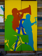 Tea Break's Over (Steve Taylor (Photography)) Tags: hammer step ladder basket helmet thecommons art graffiti mural streetart door shed blue brown green yellow red paint wood people man woman newzealand nz southisland canterbury christchurch cbd city pattern silhouette summer cycle bicycle bike cyclist