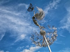Sunlight in her hair (Jeanni) Tags: fairy butterfly wire sculpture sky blue clouds silver dandelions flower fantasy
